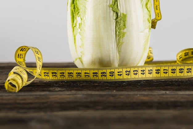 Close-up of measuring tape and lettuce on wooden surface