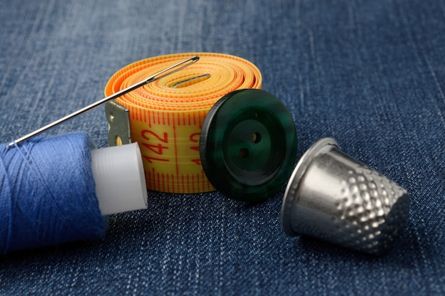 Close-up of measuring tape of spool of thread and thimble buttons