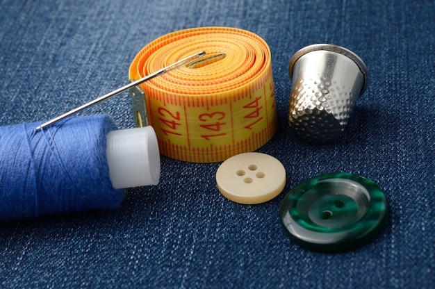Close-up of measuring tape of spool of thread and thimble buttons.