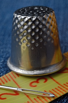 Close-up of a measuring tape and a thimble with a needle.