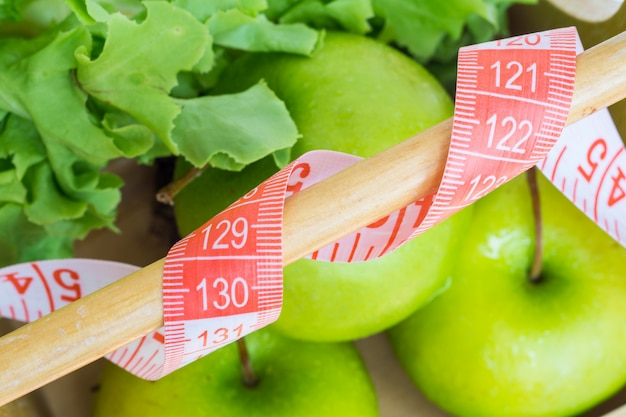 Close up of measuring tape with green apples and green oak lettuce in wood basket blurred background.