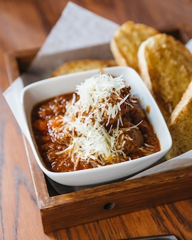 Close up meat sauce topping with mozzarella cheese, served with garlic bread.