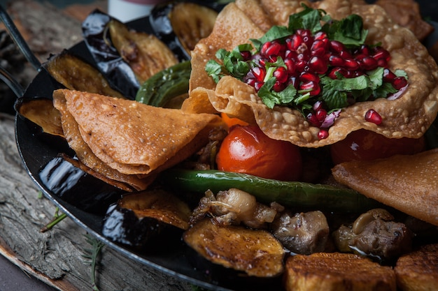 Close-up meat with baked potatoes, eggplant, tomato, pepper and decorated with pomegranate on wooden bark
