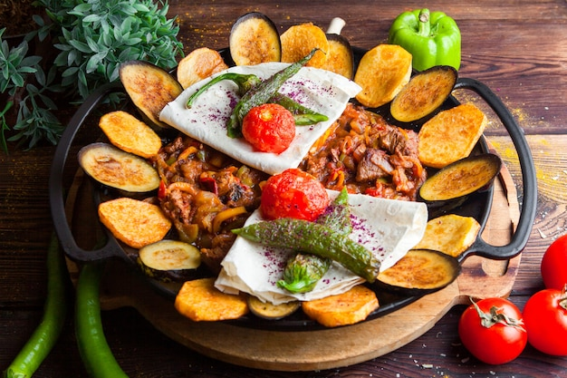Close-up meat with eggplant, tomatoes, potato, pita bread mushrooms and pepper in a round plate on a dark wooden table horizontal