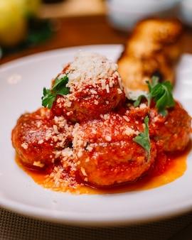 Chiuda su del piatto delle polpette guarnito con parmigiano e prezzemolo grattati della salsa al pomodoro