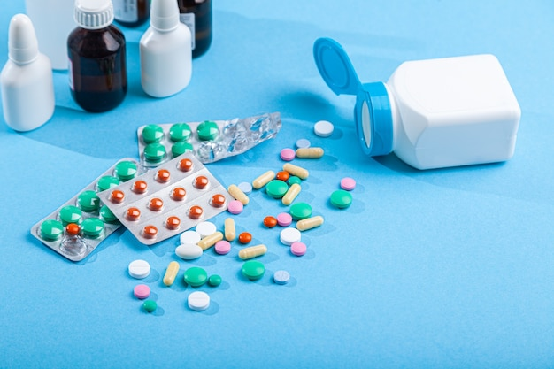 Close-up medical medicines, thermometer, syringe, spray, bottles of nose drops, syrup, scattered from pill bottle colorful tablets, capsules on blue wall, vitamins, horizontal, copy space