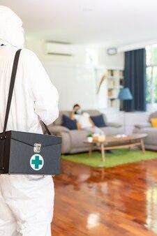 Закройте вверх медицинский персонал в костюме средств индивидуальной защиты сиз дома