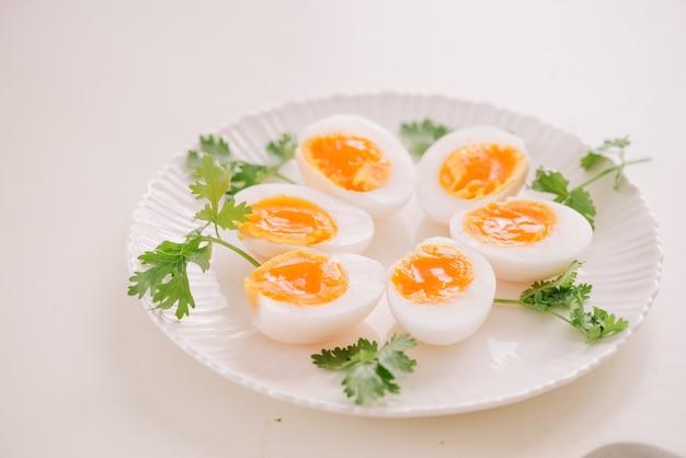 白い皿に中程度の半熟アヒルの卵の部分をクローズアップ