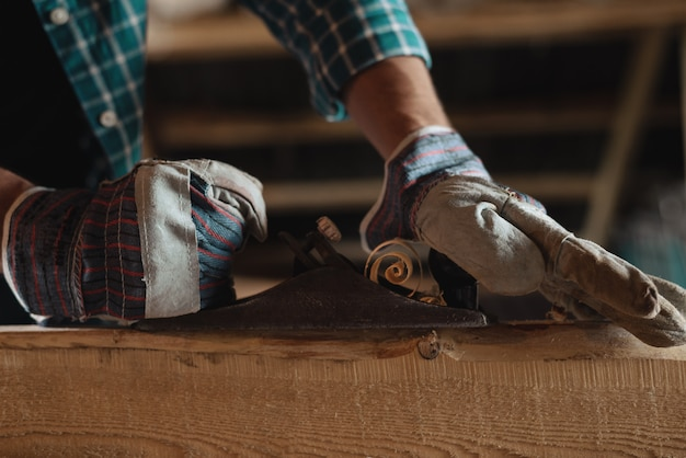 Close-up of men hands in working gloves with hand plane cut wood.