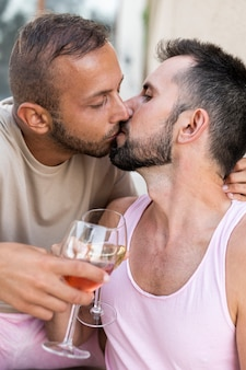 Close-up men kissing and toasting