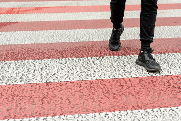 横断歩道を渡すクローズアップ男性の足