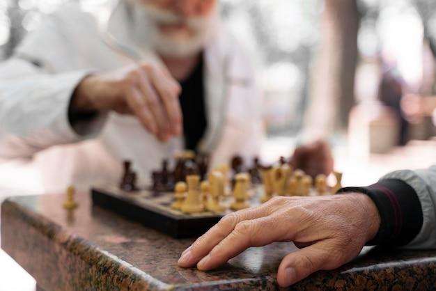 Uomini ravvicinati che giocano a scacchi all'aperto