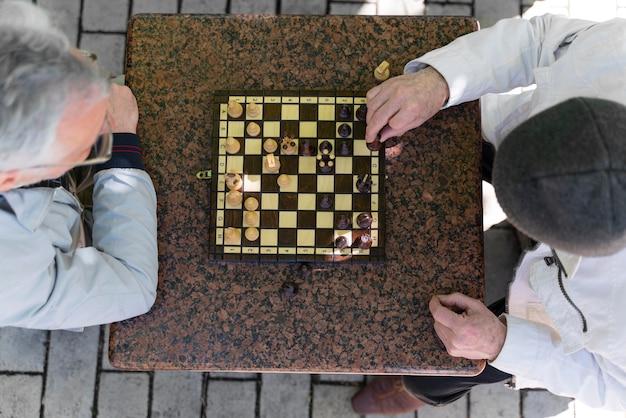 Chiuda in su uomini che giocano a scacchi insieme all'aperto