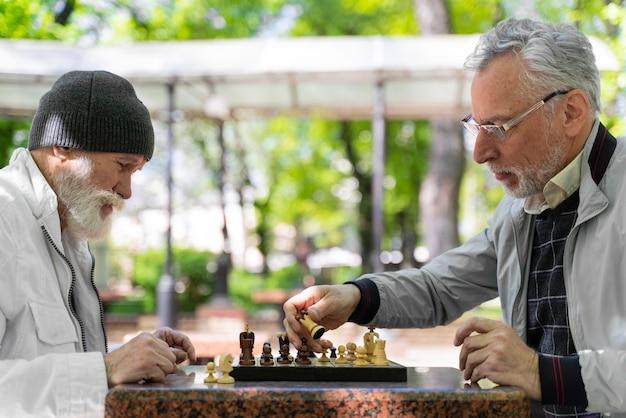 Uomini ravvicinati che giocano a scacchi insieme