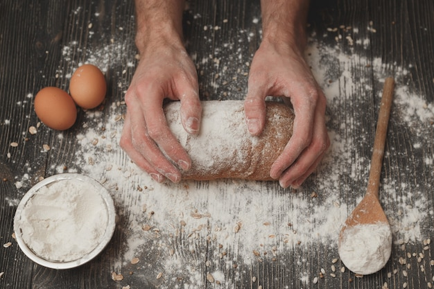 Close-up of men's baker hands on black bread with flour powder. concept of baking and patisserie.