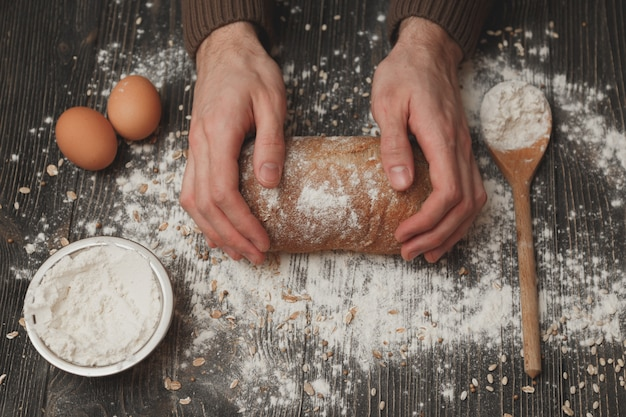 Close-up of men's hands on black bread with flour powder. baking and patisserie concept.