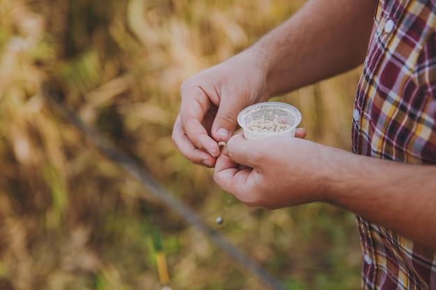 Primo piano le mani degli uomini tengono una piccola scatola con i vermi e mettono l'esca sul gancio per pescare con una canna da pesca su uno sfondo sfocato arbusti e canne. stile di vita, ricreazione del pescatore, concetto di svago.