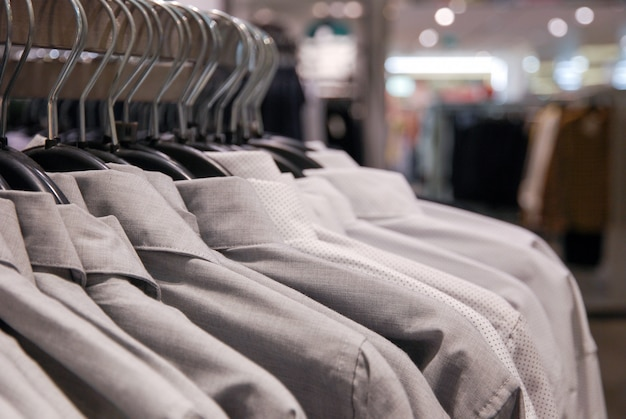 Close up of men's shirts of neutral tones on hanger in clothing store