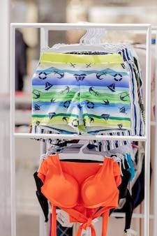 店で男性用水泳パンツと女性用水着を閉じる