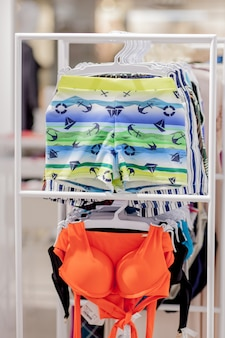 Close up men's swimming trunks and women's swimwear at the store