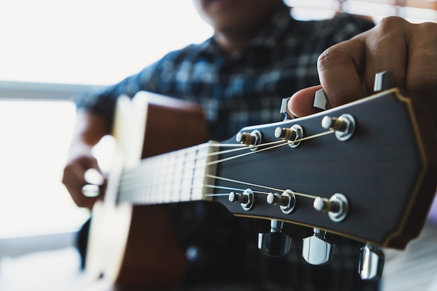 Close up men wearing blue plaid shirts are setting the guitar