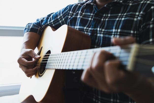 Close up men wearing blue plaid shirts playing guitar