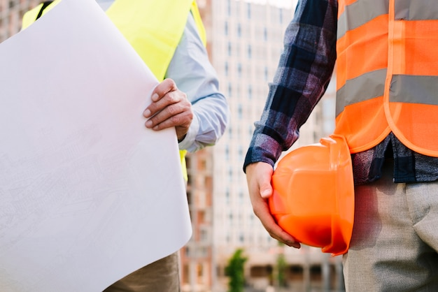 Close-up men with safety vests and helmet