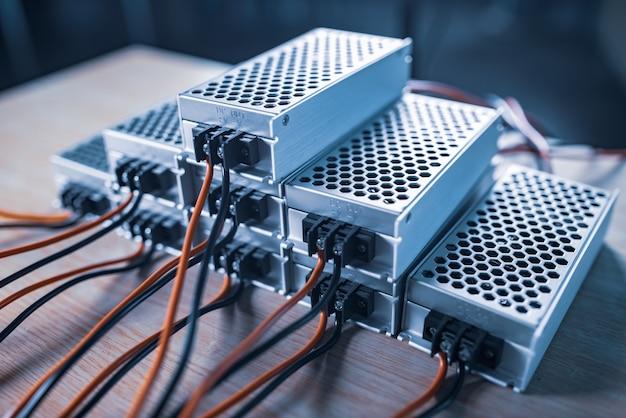 ワイヤーで電源を保管するためのクローズアップの金属ケースは、木製のテーブルの上に積み重ねられています。軍事スパイ機器用のハイテク機器の概念