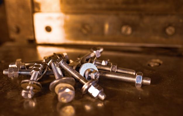 근접한 금속 크롬 볼트와 너트가 혼란스러운 순서로 기계의 반짝이는 금속 표면에 놓여 있습니다. 수리 및 예비 부품 개념