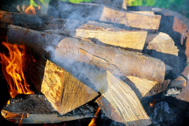 Close up on metal grill with burning wood log