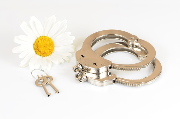 Close-up of metal handcuffs, keys and chamomile flower isolated over white background
