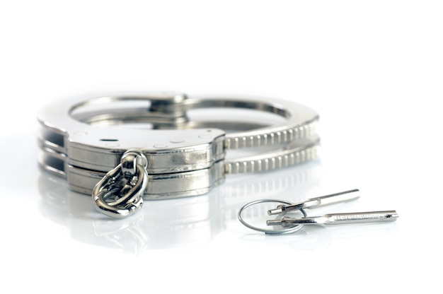Close-up of metal handcuffs and keys isolated over white surface. sexual games and practicing bdsm concept