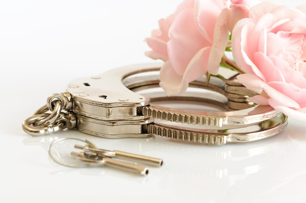 Close-up of metal handcuffs, keys and romantic pink flower