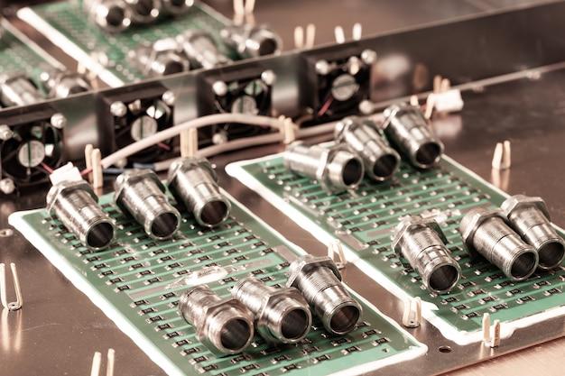 クローズアップの金属製のナットとシリンダーは、ポンプとボイラーのプラントの緑色のマイクロ回路上にあります