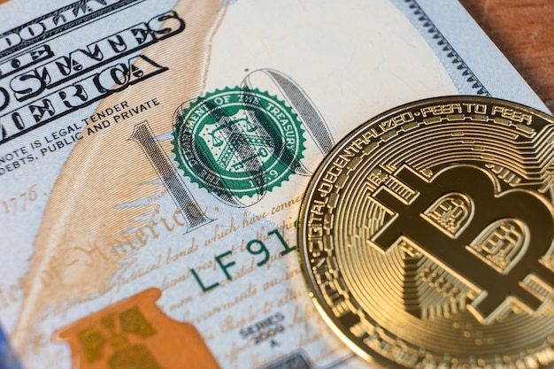 Close up of metal shiny bitcoin crypto currency coin on us dollar bills. electronic decentralized money concept.