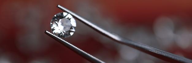 透明なダイヤモンドを保持している金属のトングを閉じる