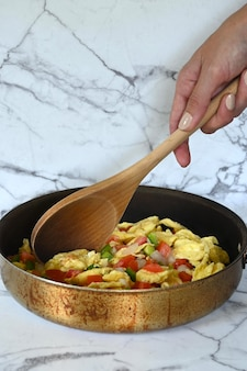 Close-up of mexican eggs in frying pan, latin young woman's hand, marble background, copy space
