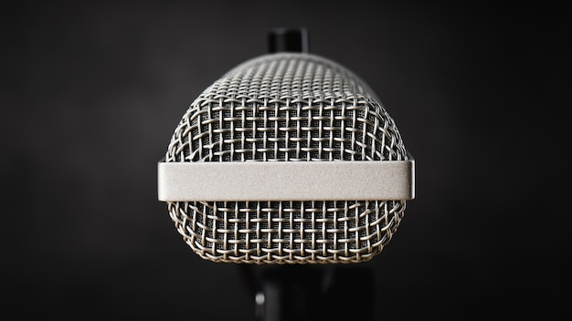 Close up microphone for audio record or podcast concept, single microphone on dark shadow background with copy space