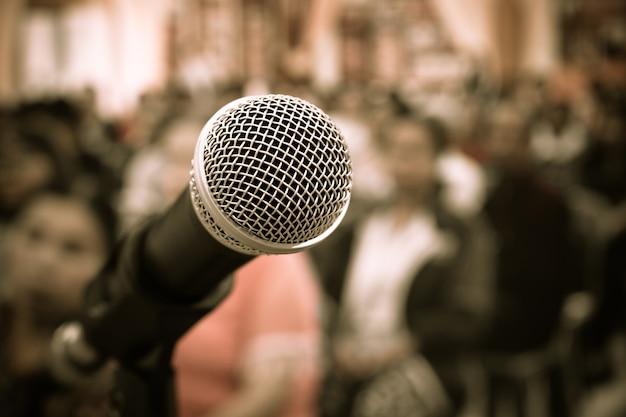 Крупным планом микрофоны на абстрактной размытой речи в зале заседаний, передняя речь blur pe
