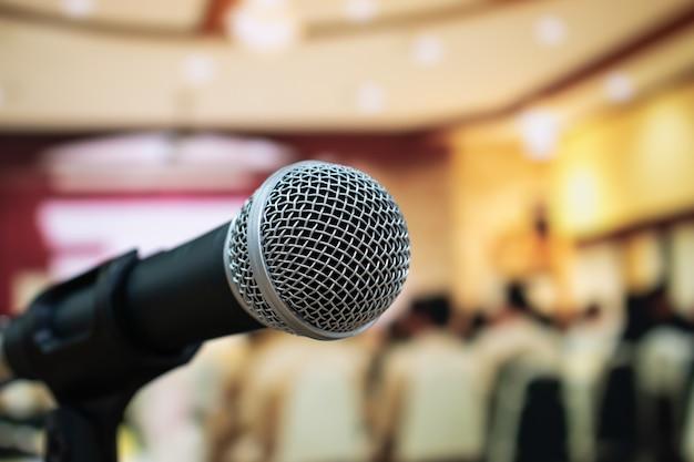 Крупным планом микрофоны на абстрактной размытой речи в зале заседаний