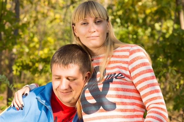 背景に緑の木々と彼らの自由な時間の間に公園で中年の白人のロマンチックなカップルを閉じます。
