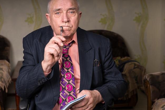 Крупным планом лысый бизнесмен средних лет, держа ручку у уголка рта и мелкие заметки, серьезно глядя в камеру