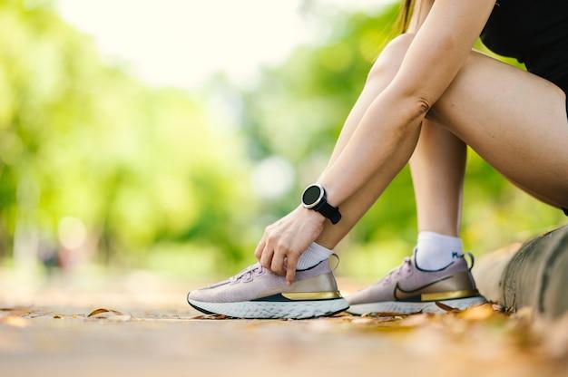 美しい夏の日に屋外で靴ひもを結ぶ中年の美しいスポーツアジアの女性を閉じます。