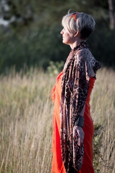 Close-up of a middle-aged blond woman standing in a meadow facing the sun and meditating.