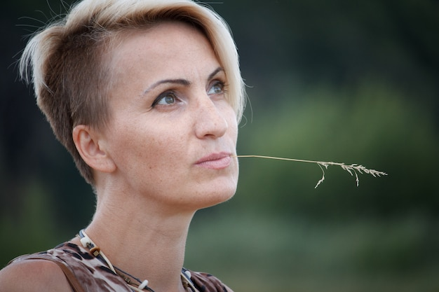 Close-up of a middle-aged blond woman with a spikelet in her mouth.