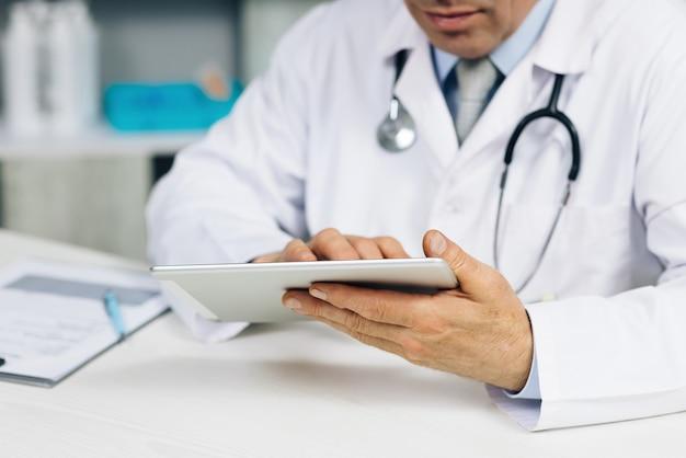 환자 방문을 관리하는 손에 디지털 컴퓨터 태블릿을 들고 흰색 제복을 입은 중간 나이 든 남성 의사를 닫습니다