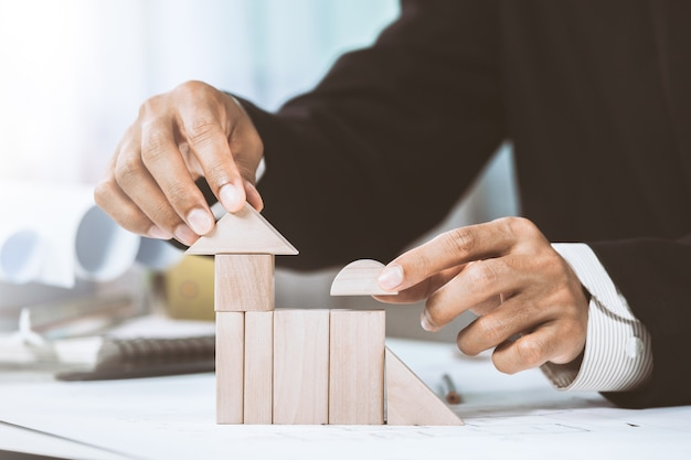 Close-up midsection of businessperson making house model with wooden blocks on construction plan