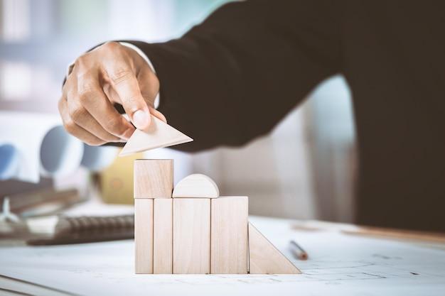 Крупный план среднего предпринимателя, делающего модель дома с деревянными блоками на плане строительства