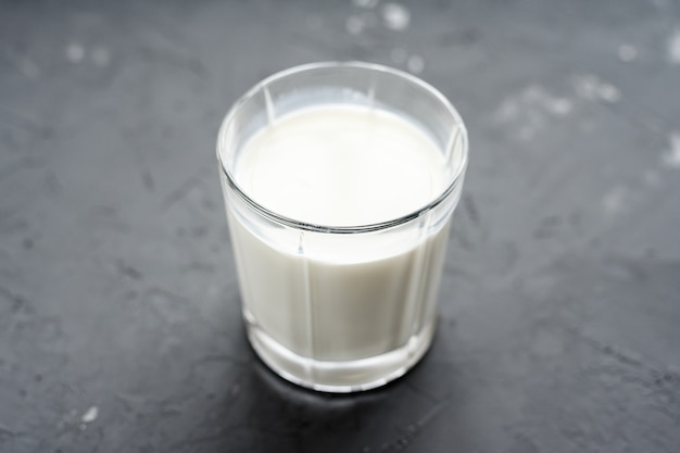 Close-up of milk in glass cup on grey background. dairy product