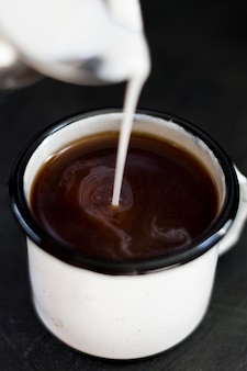 Close up milk pourred in black coffee